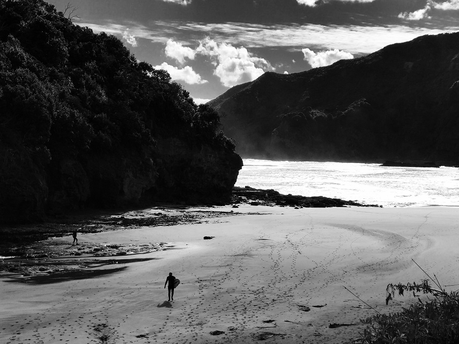 Black and white image of a surfer on Bethells Beach near Te Henga Walkway